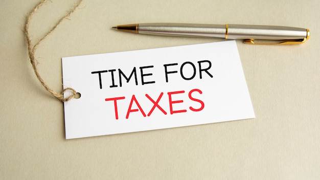 White card with text time for taxes with metal pen on gray background.