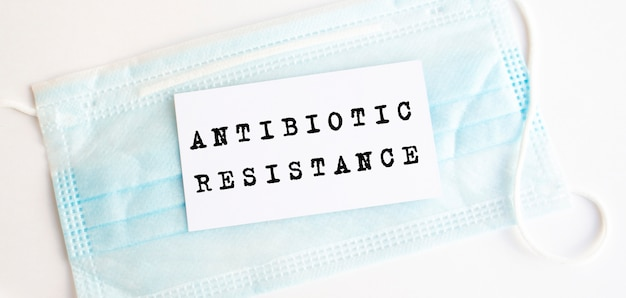 Белая карточка с надписью устойчивость к антибиотикам на медицинской защитной маске.