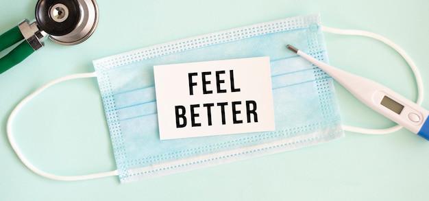 医療用保護マスクにfeelbetterの刻印が入った白いカード。医療の概念。