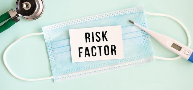 의료 보호 마스크에 risk factor라는 글자가 있는 흰색 카드.