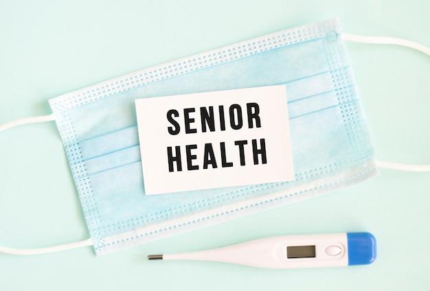 医療用保護マスクにシニアヘルスの刻印が入った白いカード