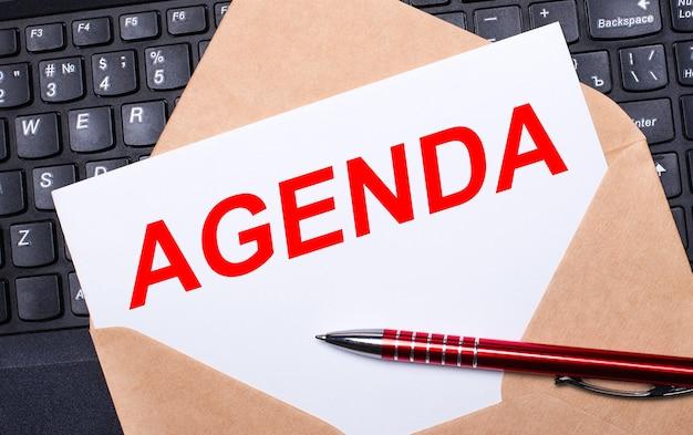 Белая карточка с текстом повестка дня в крафтовом конверте на рабочем столе с современной клавиатурой ноутбука и бордовым пером. плоская планировка рабочего места.