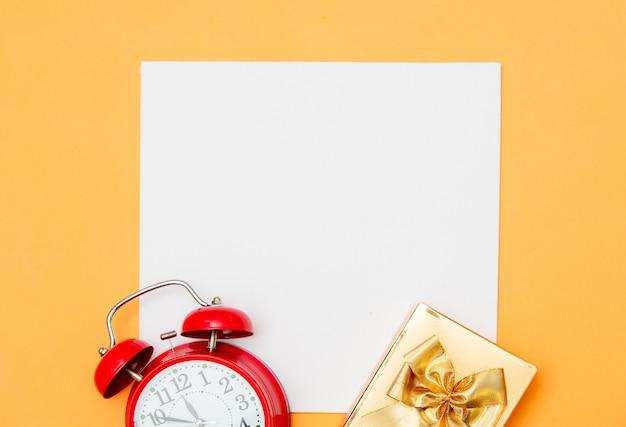 Белый картон и будильник с подарочной коробкой на желтом