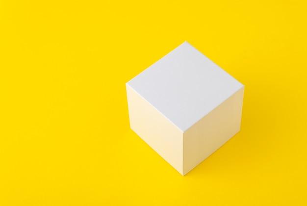 黄色の背景に正方形の白い段ボール箱。スペースをコピーします。モックアップ。