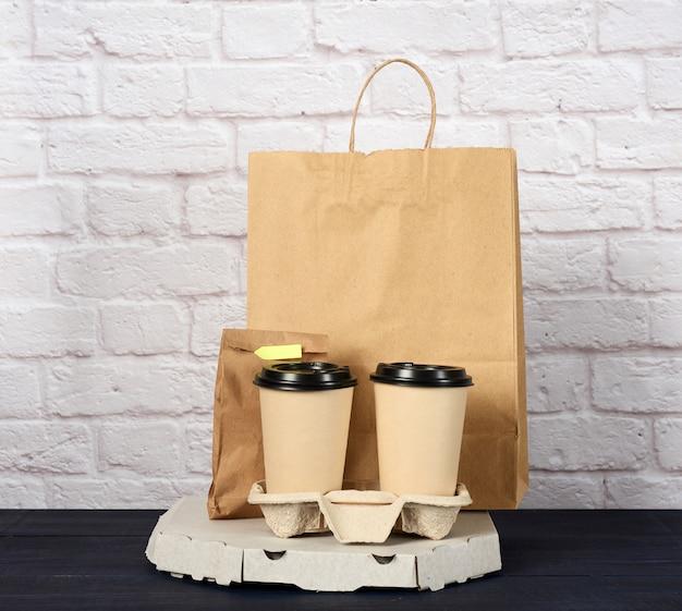Белая картонная коробка с пиццей и одноразовые бумажные стаканчики с кофе в держателе