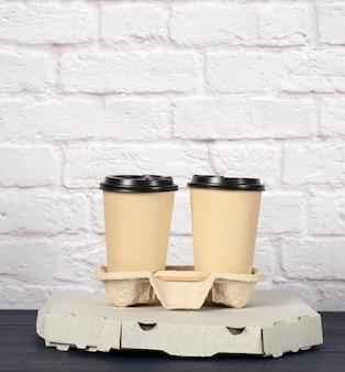 Белая картонная коробка с пиццей и одноразовыми бумажными стаканчиками