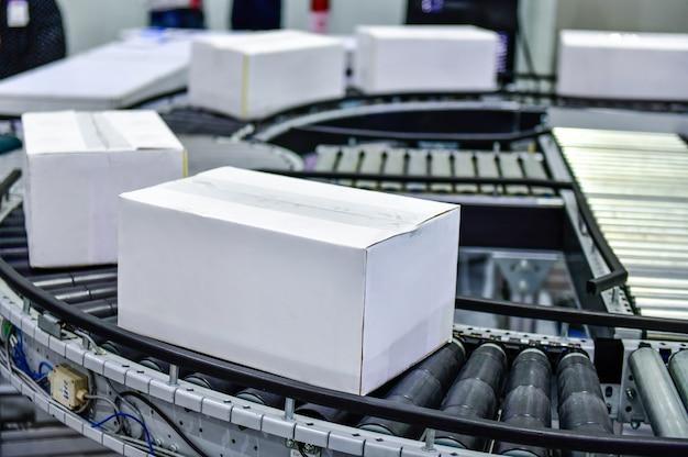 Белые картонные коробки на концепции системы транспортировки посылок конвейерной ленты
