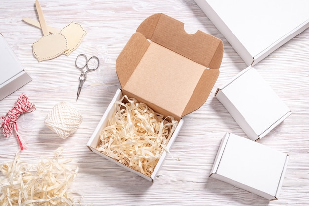 Белая картонная коробка на деревянном столе, плоский макет