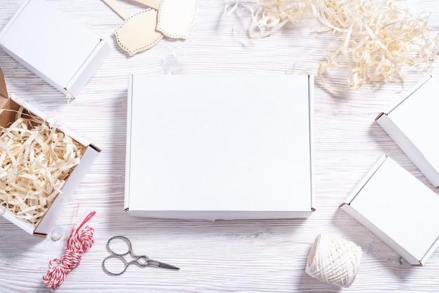 Белая картонная коробка на деревянном столе,