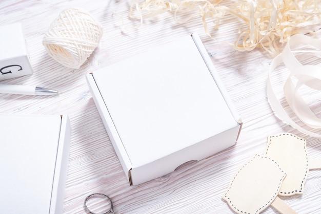 White cardboard carton box on wooden desk, flat lay mock up