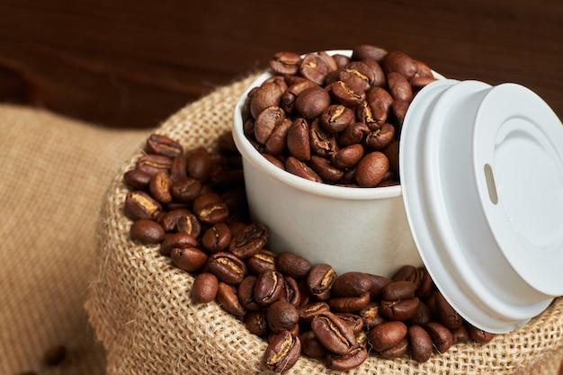 焦げた木製のテーブルにニットバッグにコーヒー豆と白い段ボールカップ