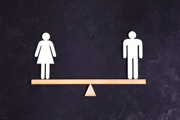 Белые картонные гендерные фигурки стоят на качелях