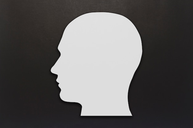 White cardboard head on a black background. copy space. flat lay, top view.