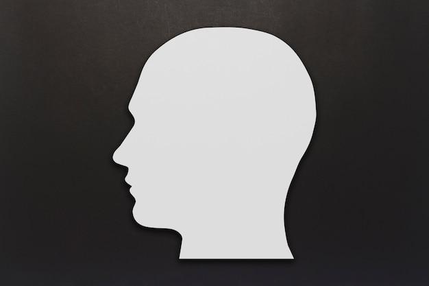 Белая картонная голова на черном фоне. копировать пространство плоская планировка, вид сверху.