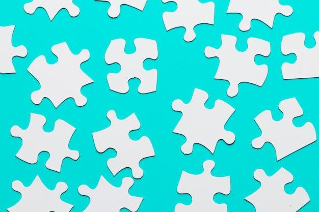 ターコイズブルーの背景に白いボール紙ジグソーパズルのピース