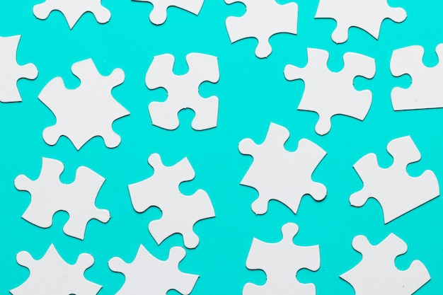 White cardboard jigsaw puzzles pieces on turquoise backdrop