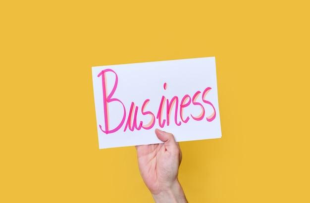 Белый картон с рукописным текстом. слово бизнес. на желтом изолированном фоне.