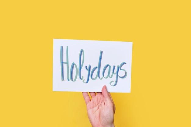 Белый картон с рукописным текстом. слово праздники. на желтом изолированном фоне.