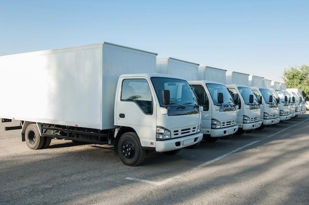 주차장에 흰색 화물 차량이 줄지어 서 있습니다. 화물 운송. 트럭 공원