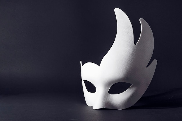 White carnival mask on a black background. concept of carnival, holiday, festival.