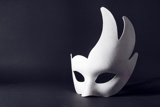 검정색 배경에 흰색 카니발 마스크입니다. 카니발, 휴일, 축제의 개념입니다.