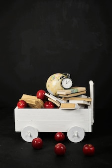 A white cart with a books globe and apples on a black background