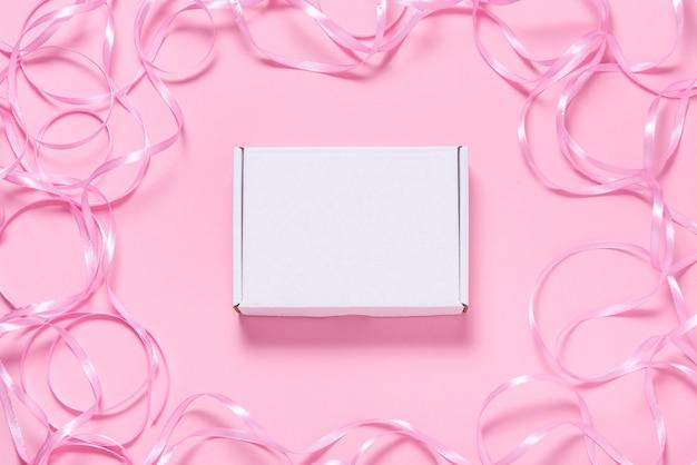 핑크 리본으로 장식 된 흰색 판지 상자