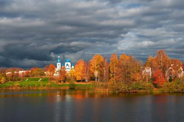 黄金の秋の木々に囲まれた遠くにある白い大聖堂。ガッチナ旧市街。ロシア。