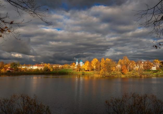 黄金の秋の木々に囲まれた遠くにある白い大聖堂。嵐の前の村。ガッチナ旧市街。