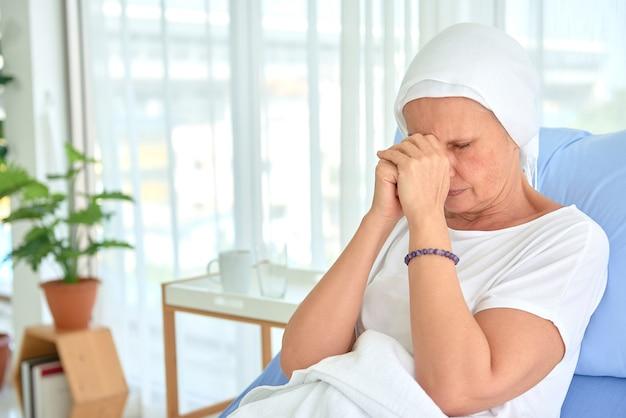 Белые кавказские женщины без волос и бровей плохо себя чувствуют, молятся и ждут химиотерапии в больничной палате, концепции месяца осведомленности о раке груди.