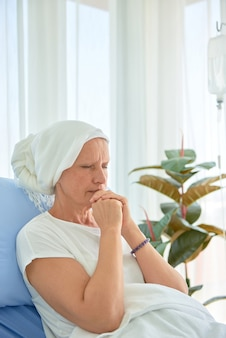 White caucasian female hairless and eyebrowless feel bad are praying and waiting for chemotherapy  in hospital room, breast cancer awareness month concept.