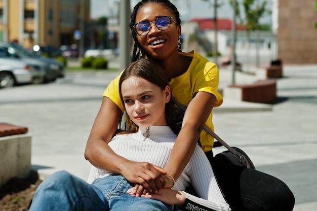 白い白人の女の子と黒いアフリカ系アメリカ人が一緒に。世界の統一、人種的愛、寛容の理解、多様性協力の競争