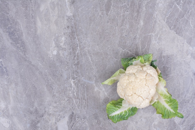 White cauliflower with green leaves on marble.
