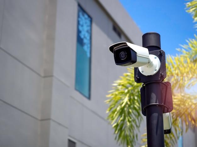 Белые камеры видеонаблюдения на черном столбе в саду возле здания
