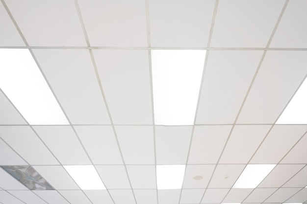 蜂起ビューのネオン電球と白い天井。テキストやデザインのコピースペースと背景の室内装飾のコンセプトとして。
