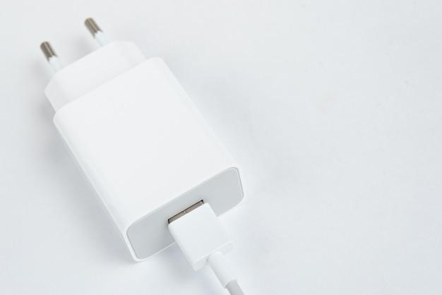 白い孤立した背景に白い携帯電話の充電器-usbcabe付き