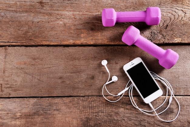 木製のヘッドフォンとピンクのダンベル付きの白い携帯電話