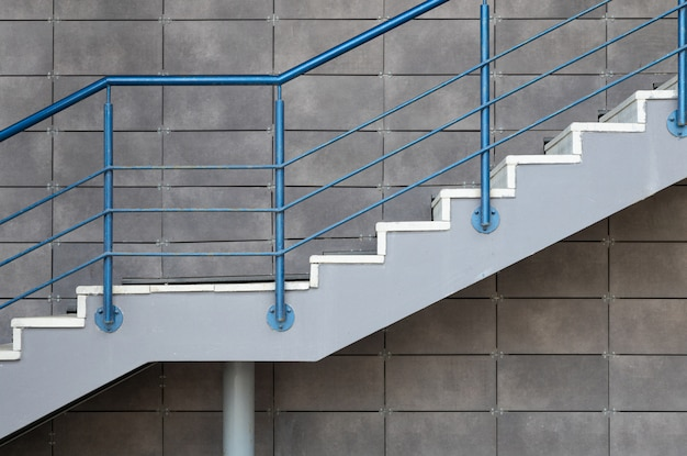 White cement stairs with blue steel railing on gray tiled wall background