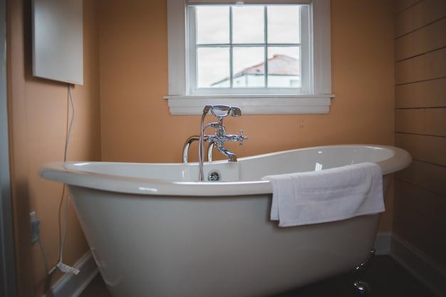 Белая керамическая ванна у окна