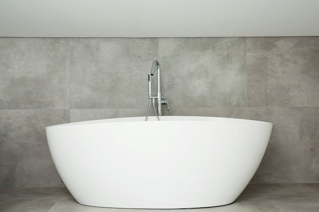 White ceramic bathtub with a steel faucet on grey background