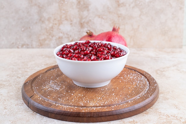 White ceramic bowl full with fresh pomegranate seeds on wooden board.