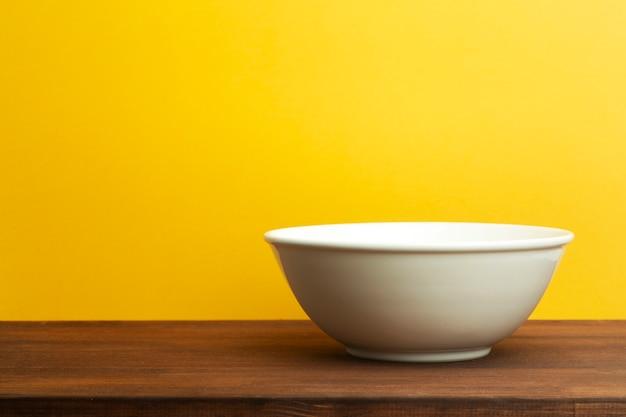 黄色の背景に白いセラミックボウル。木製のテーブルのサラダやスープの空のプレート