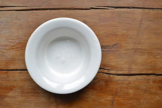 ヴィンテージの木製のテーブルに白いセラミックボウル
