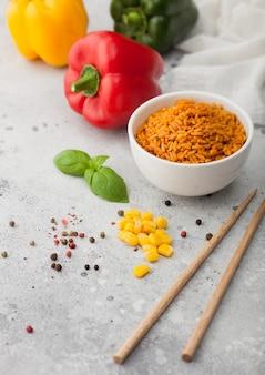 スティックとパプリカペッパーとトウモロコシ、ニンニク、バジルと明るい背景に野菜と茹でた赤い長粒バスマティライスと白いセラミックボウルプレート。
