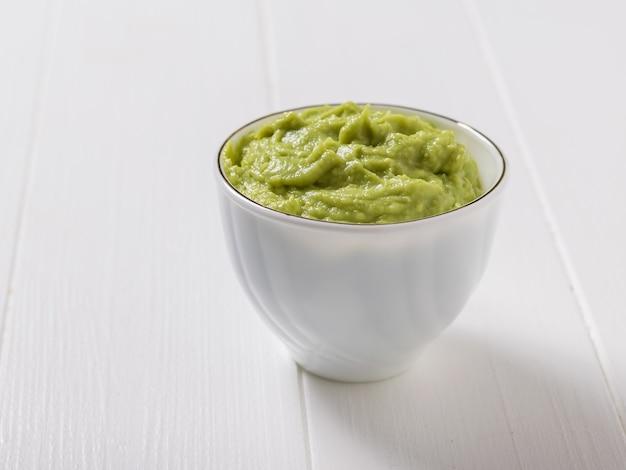 흰색 나무 테이블에 아보카도가 있는 흰색 세라믹 그릇. 다이어트 채식 멕시코 음식 아보카도. 날 음식.