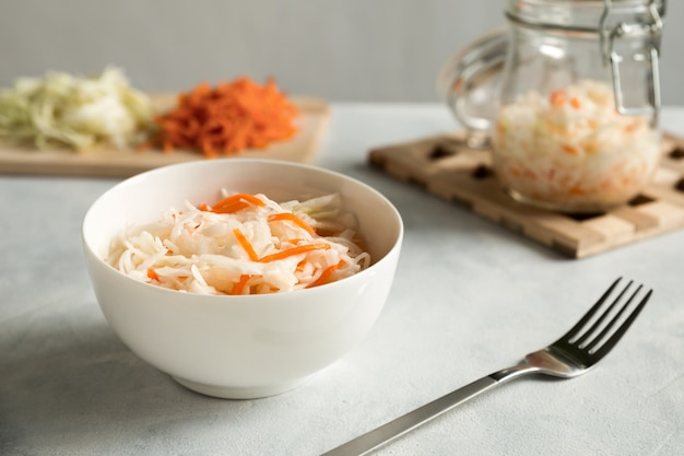 White ceramic bowl with homemade appetizer sauerkraut close up on a gray concrete