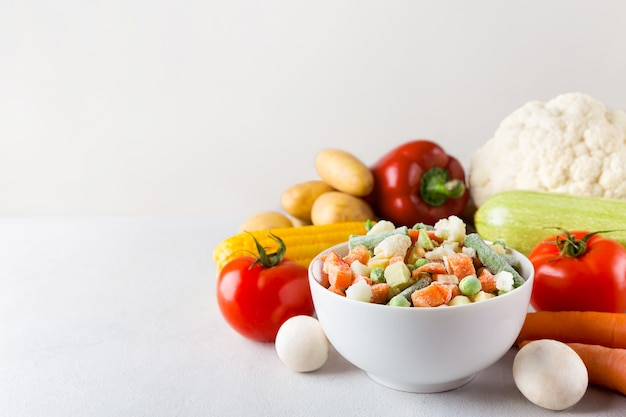 Белая керамическая миска со смесью замороженных овощей с копией пространства на сером фоне и свежими продуктами