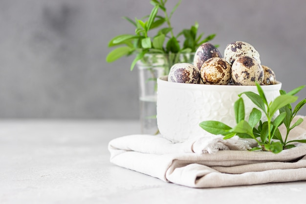 White ceramic bowl with organic quail eggs on linen napkin and green leaves