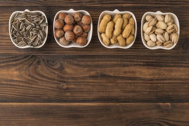 Белые керамические миски с орехами и семенами на деревянном столе. смесь орехов и семян. плоская планировка.