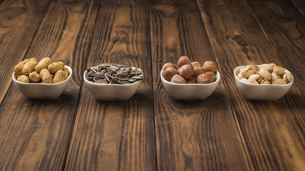 White ceramic bowls with nuts and seeds on a wooden table. a mixture of nuts and seeds.